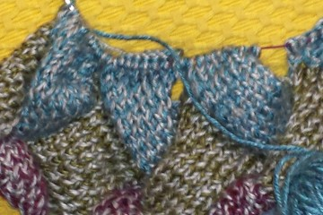 a large circular knitting needle with kntted entrelac squares in blue, green and burgundy